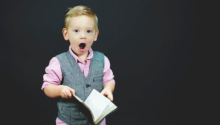 Un enfant tient un livre dans les mains. Il a l'air très étonné !