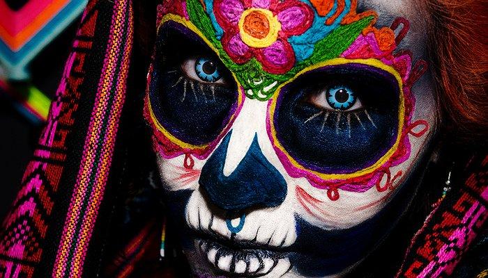 Un visage de femme maquillé de couleurs vives, façon dia de los muertos