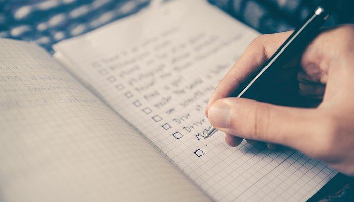 Une main tient un stylo au dessus d'une feuille de papier