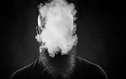 Un homme avec une barbe souffle un nuage de fumée