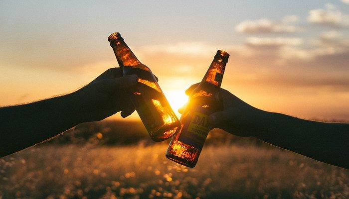 Photographie de deux personnes trinquant avec des bouteilles de bière durant un coucher de soleil.