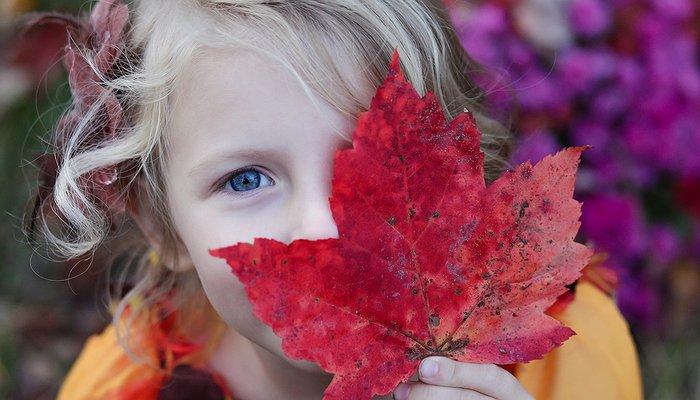 Une enfant tient une feuille d'arbre devant son visage