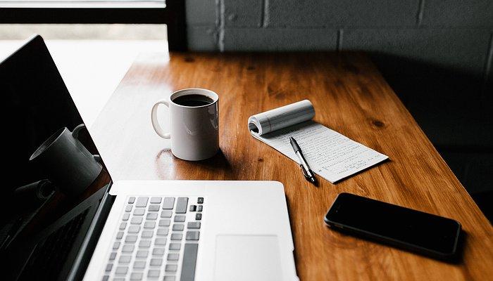 Un laptop avec une tasse de café et un bloc note