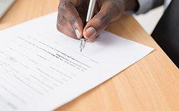 Une main tient un stylo et signe un contrat