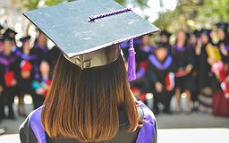 Une femme de dos porte un chapeau de graduation
